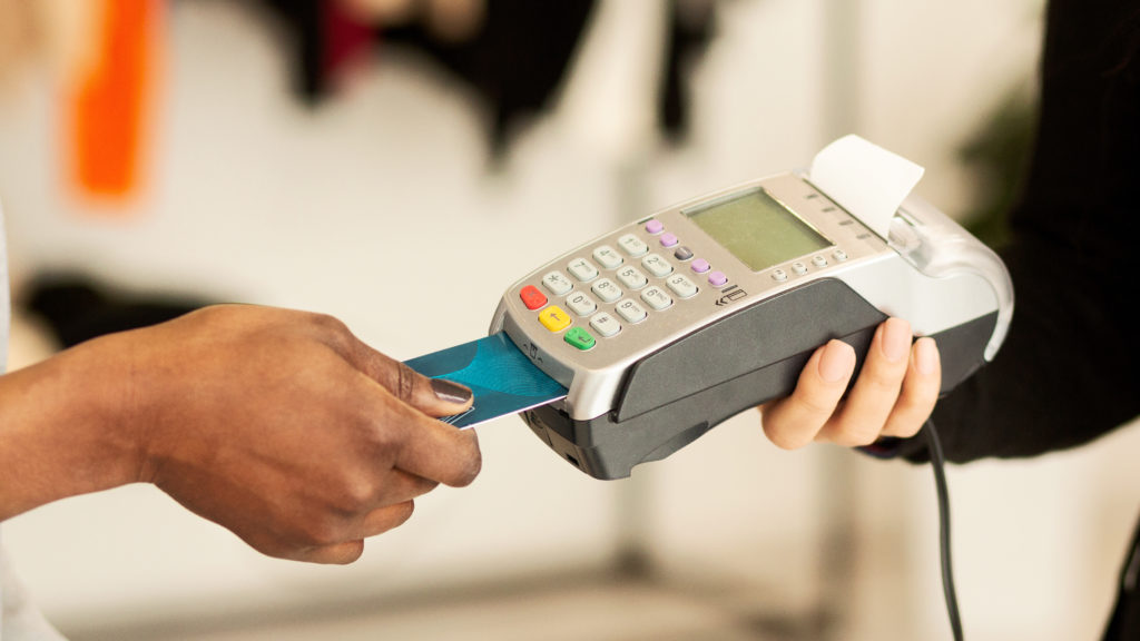 customer-paying-for-clothes-by-credit-card-in-X8S2CQE